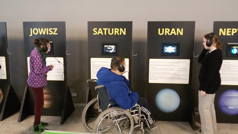 Grupa zwiedza instalację o planetach